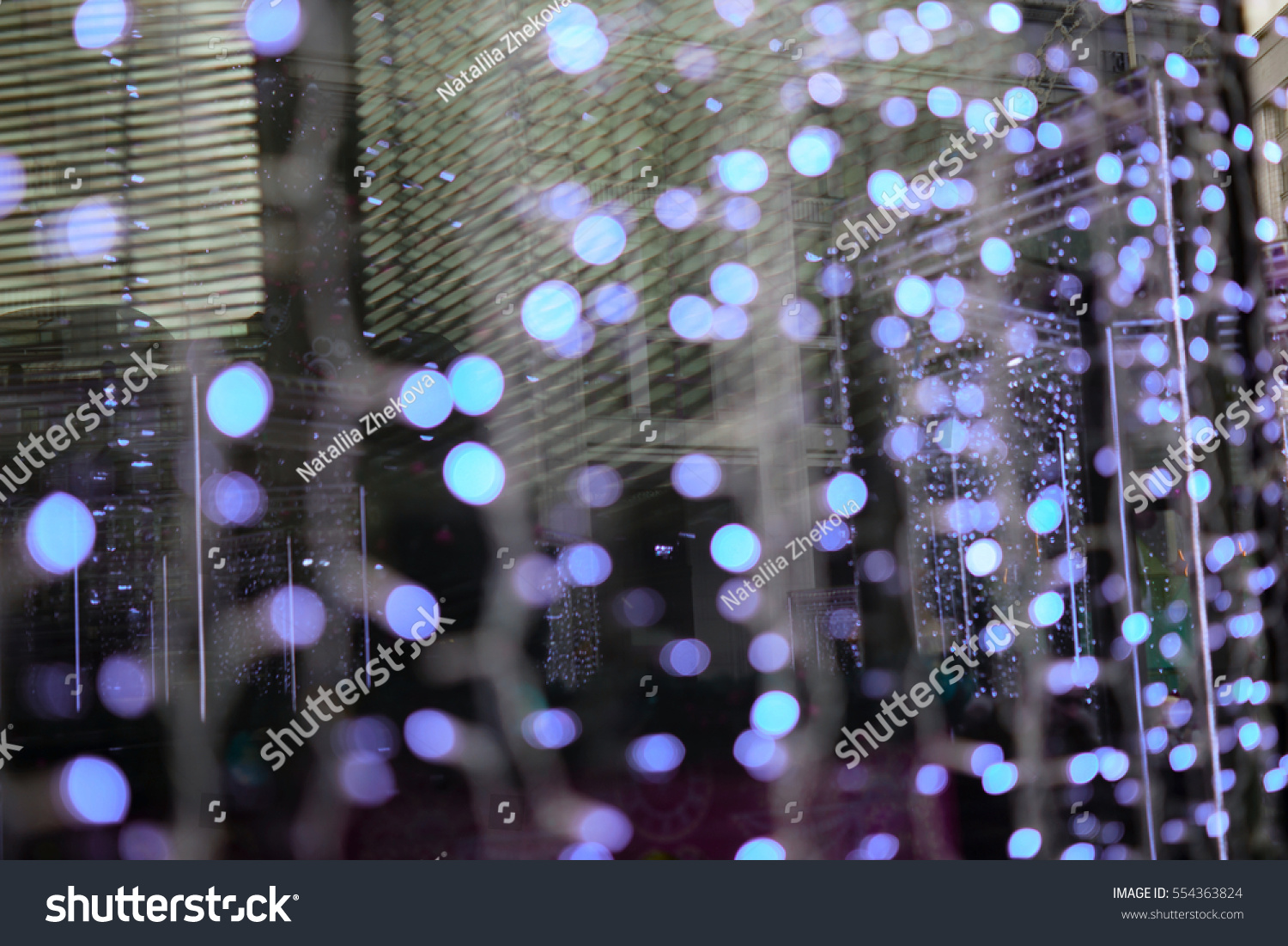beautiful bokeh background for design christmas fair lights in the windows of stores outdoors