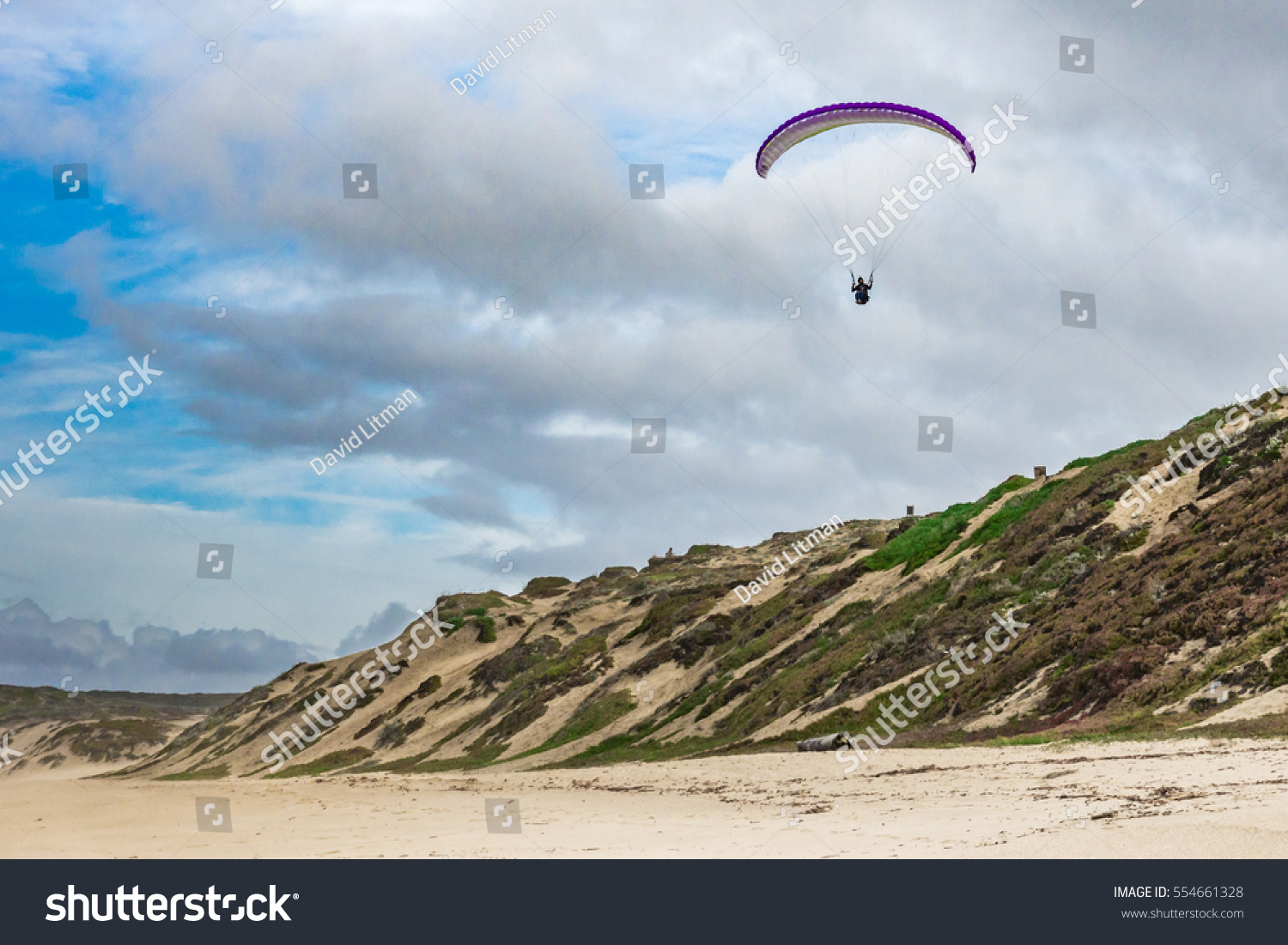 A hang glider/paraglider flies over coastal sand dunes along the Pacific Coast of central California in Sand City near Marina, along the Monterey Bay.