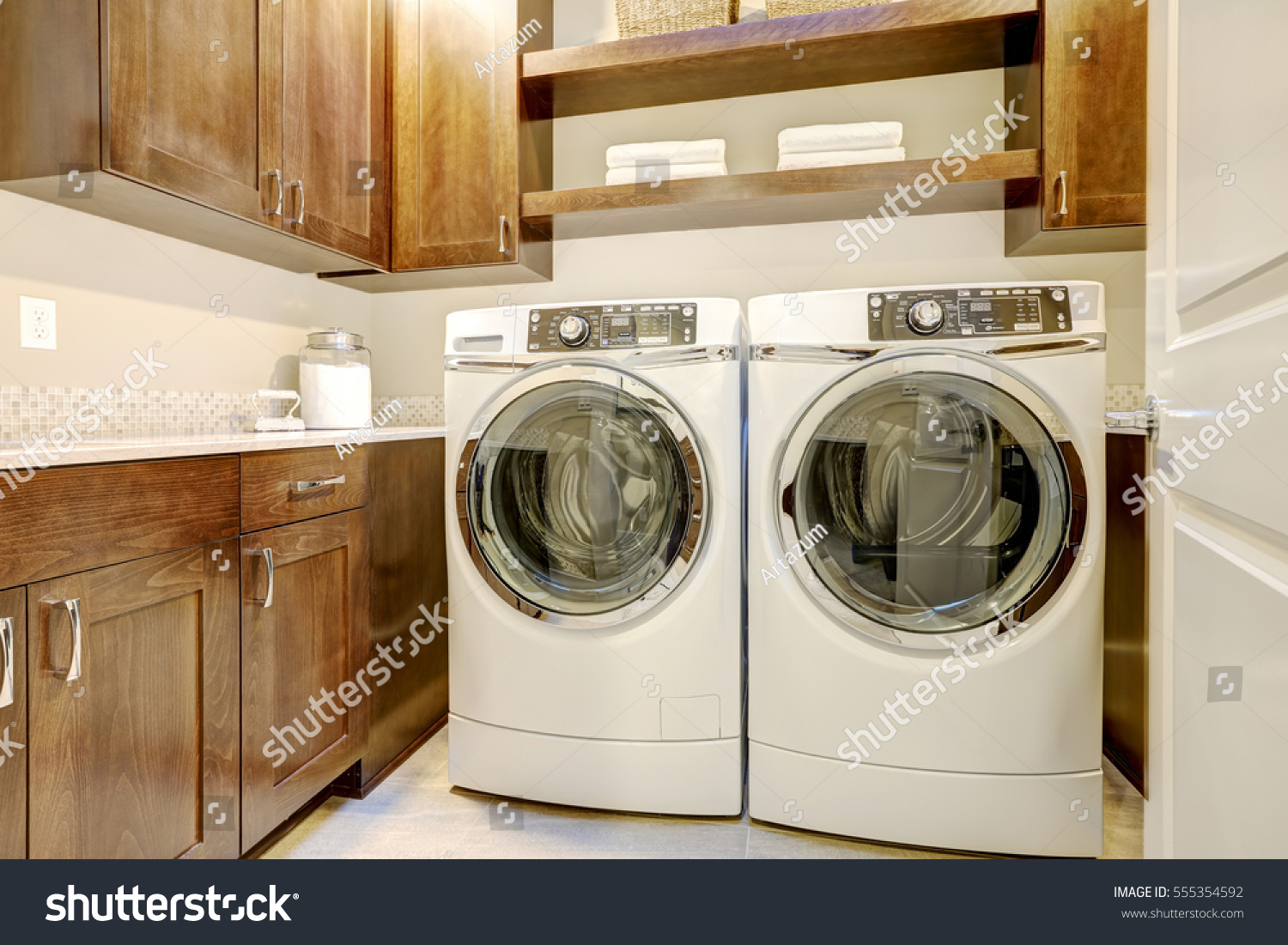 White And Brown Laundry Room Features Modern Appliances Placed Under  Shelves And Cabinets. Northwest,