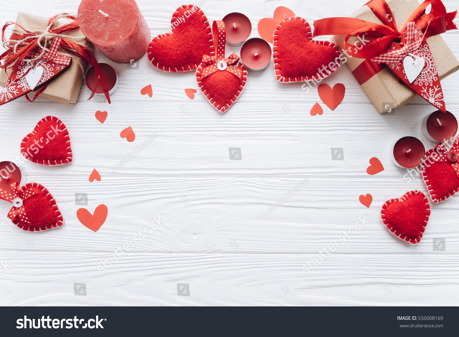 Wooden white background with red hearts, gifts and candles. The concept of Valentine Day.