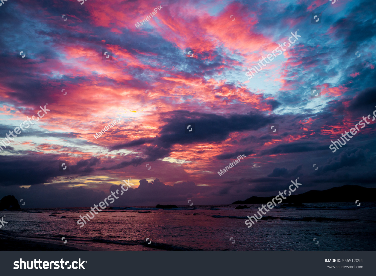 Sunset seascape with dramatic sky and colorful clouds #556512094