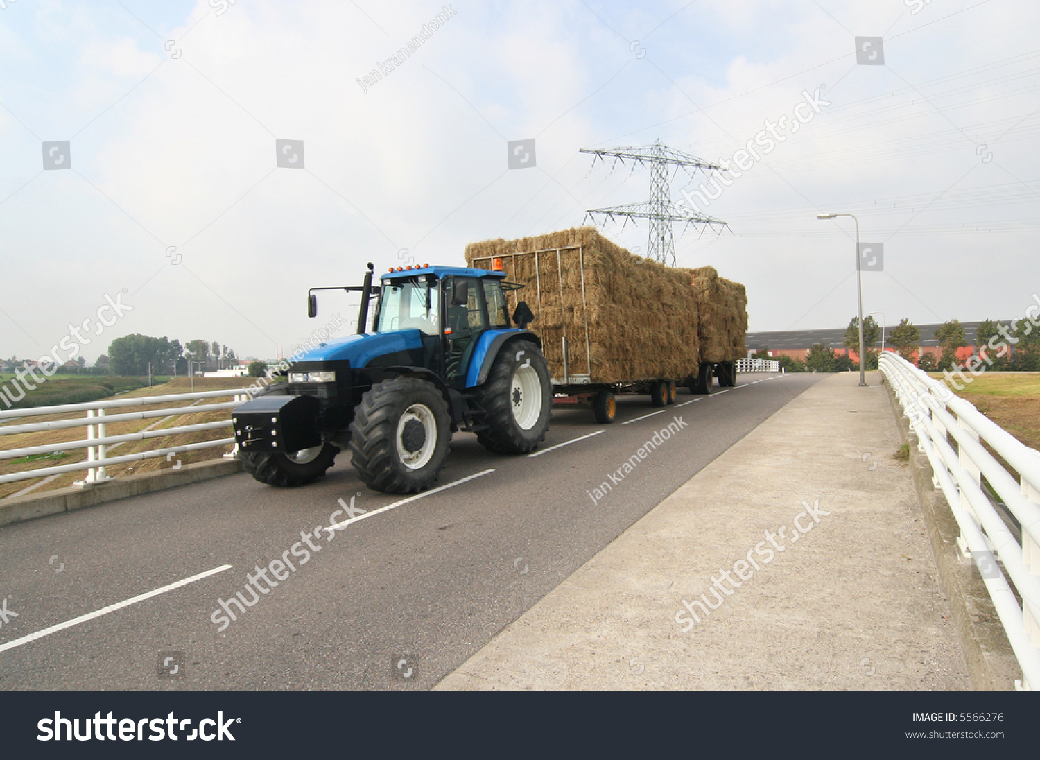Tractor Pulling Trailer : Tractor pulling a trailer with hay across bridge stock