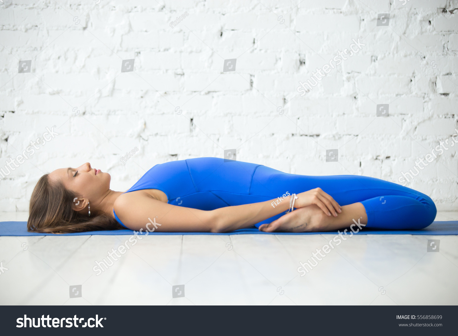 Young attractive woman practicing yoga lying in Reclining Hero exercise Supta Virasana pose & Young Attractive Woman Practicing Yoga Lying Stock Photo 556858699 ... islam-shia.org