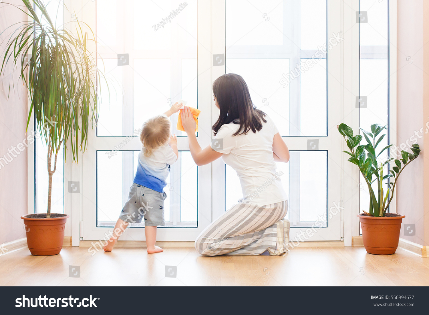 Happy family doing house cleaning young stock photo for House cleaning stock photos