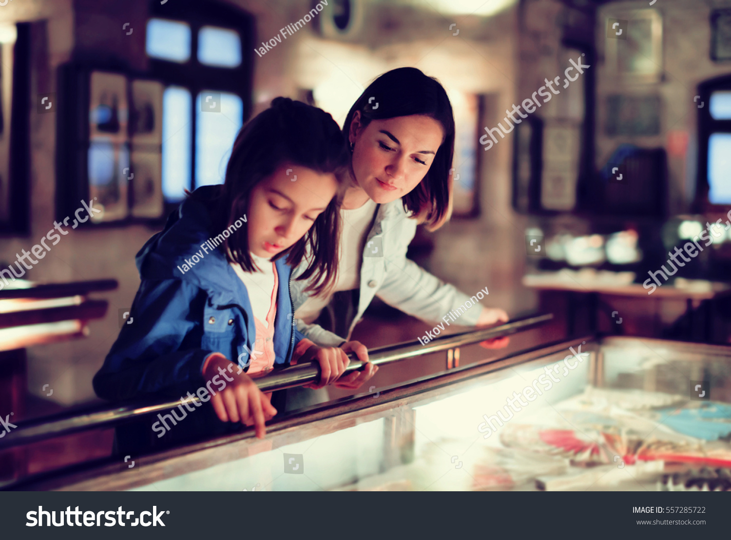 Attractive mother and daughter exploring expositions of previous centuries in museum. Focus on the woman #557285722