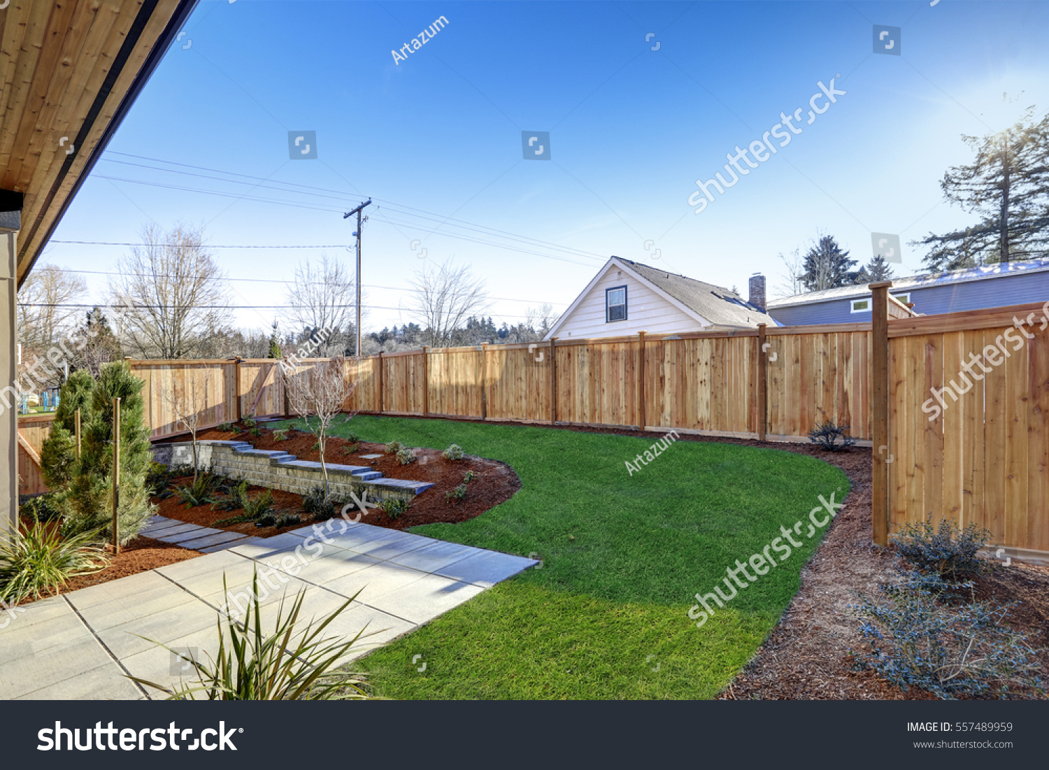 Sloped backyard surrounded by wooden fence stock photo for Luxury fences
