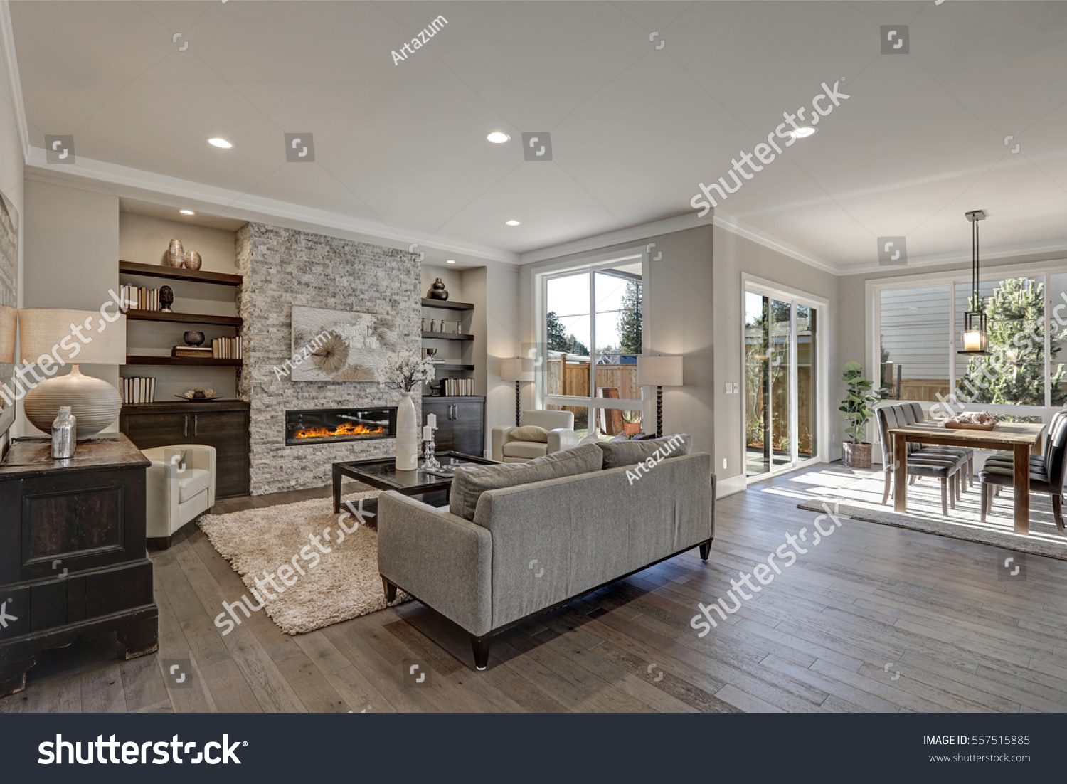 Living room interior in gray and brown colors features gray sofa atop dark hardwood floors facing stone fireplace with built-in shelves. Northwest, USA  #557515885