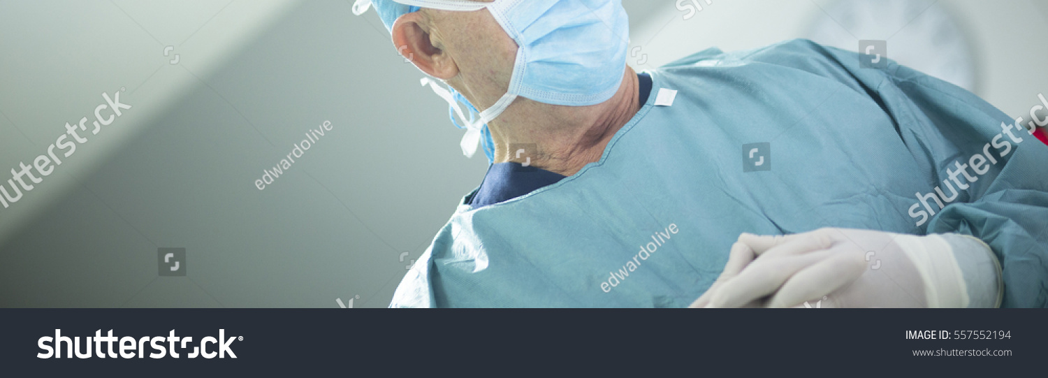 "Surgeon in hospital surgery in sterile uniform ""scrubs"" and mask in operating theater emergency room in surgical operation. #557552194"
