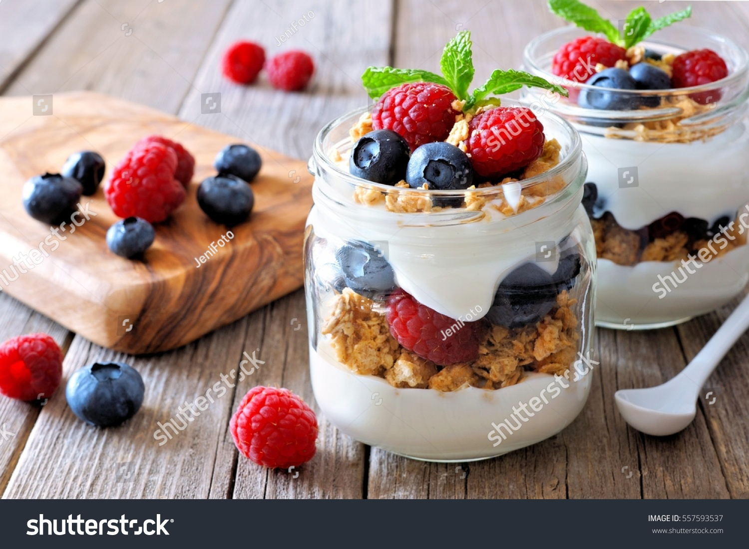 Blueberry and raspberry parfaits in mason jars, scene on a rustic wood background #557593537