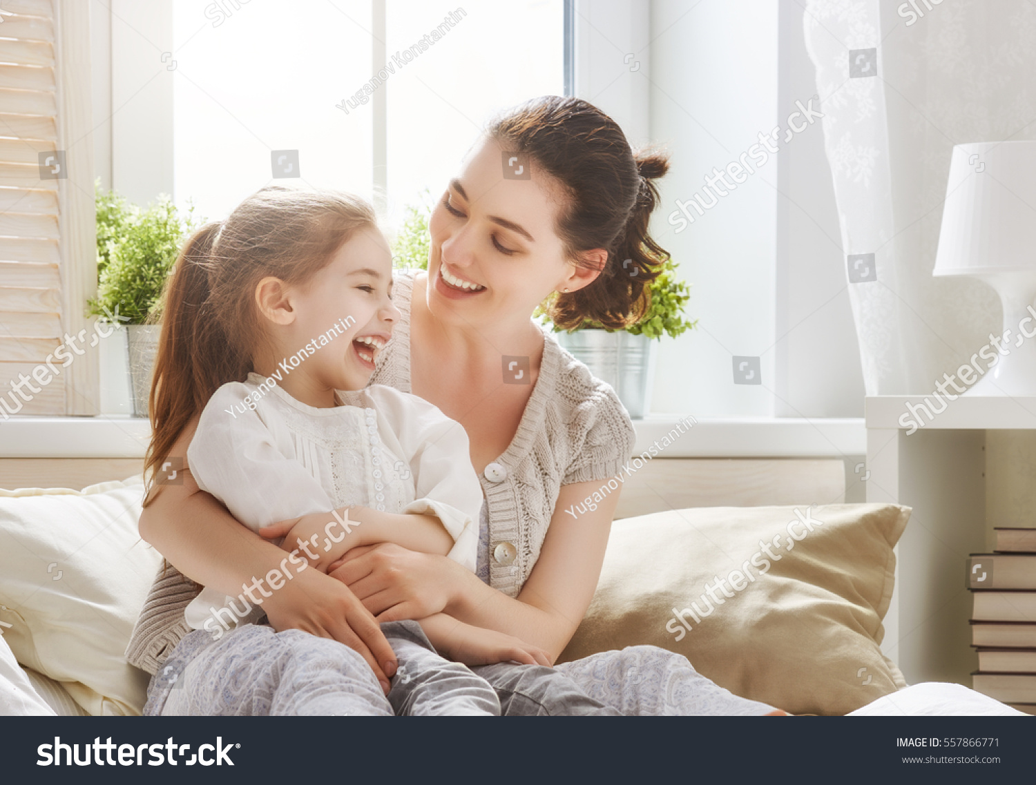 Happy loving family. Mother and her daughter child girl playing and hugging. #557866771