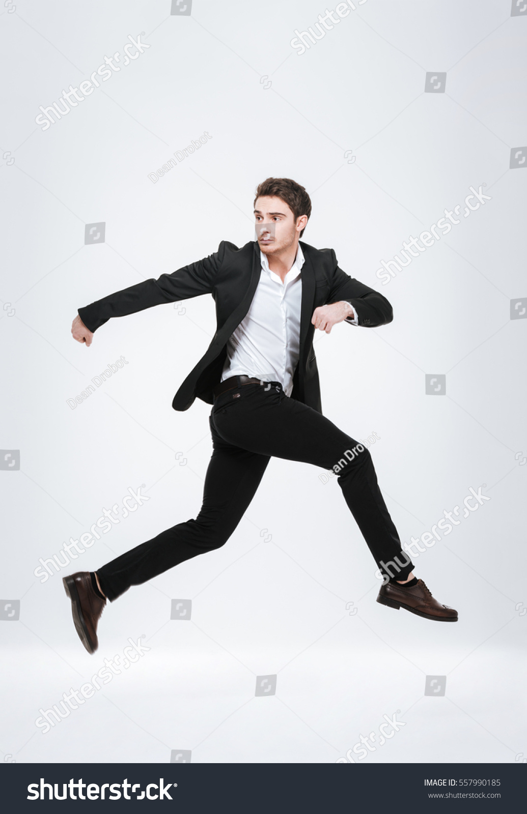 47f52ec13d Full length business man in black suit jumping in studio isolated on a white  background.