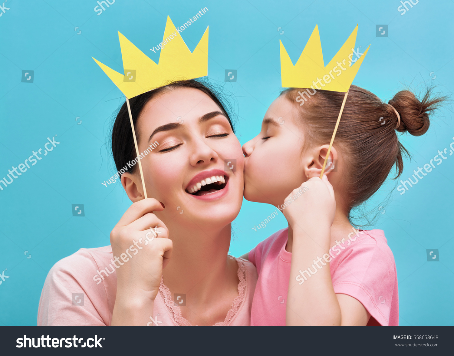 Funny family on a background of bright blue wall. Mother and her daughter girl with a paper accessories. Mom and child are holding paper crown on stick. #558658648