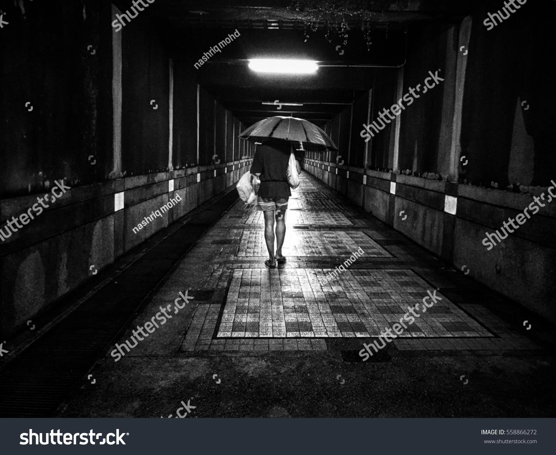 Man in a rain walking with umbrella unrecognizable person in motion blur