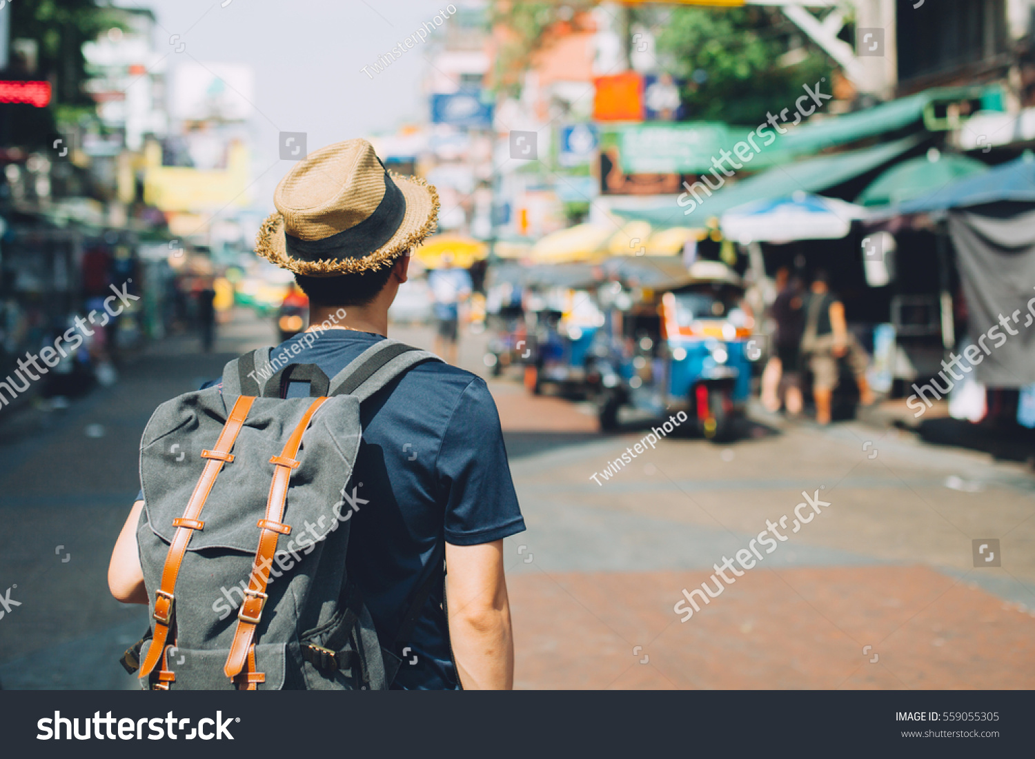 Young Asian traveling backpacker in Khaosan Road outdoor market in Bangkok, Thailand