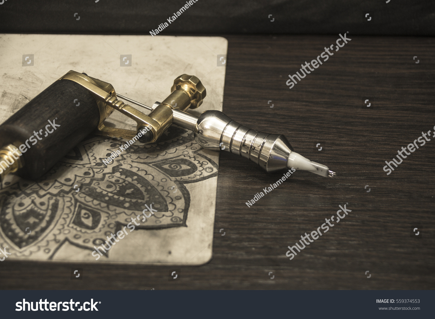 Tattoo Machine With Ink And Sketches On Tattoo Skins On Dark Wooden