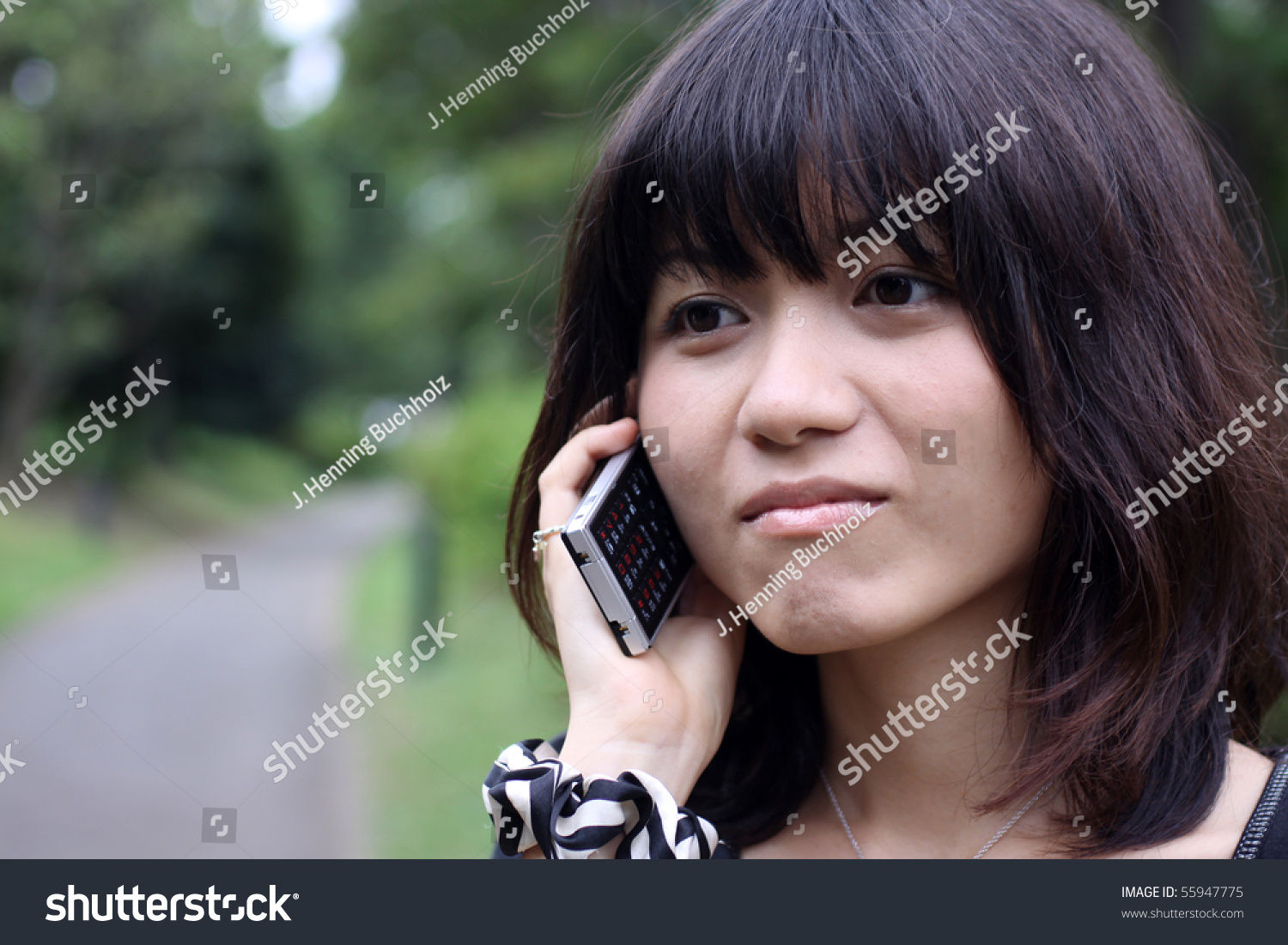 beautiful japanese girl on cellphone outdoors stock photo (edit now