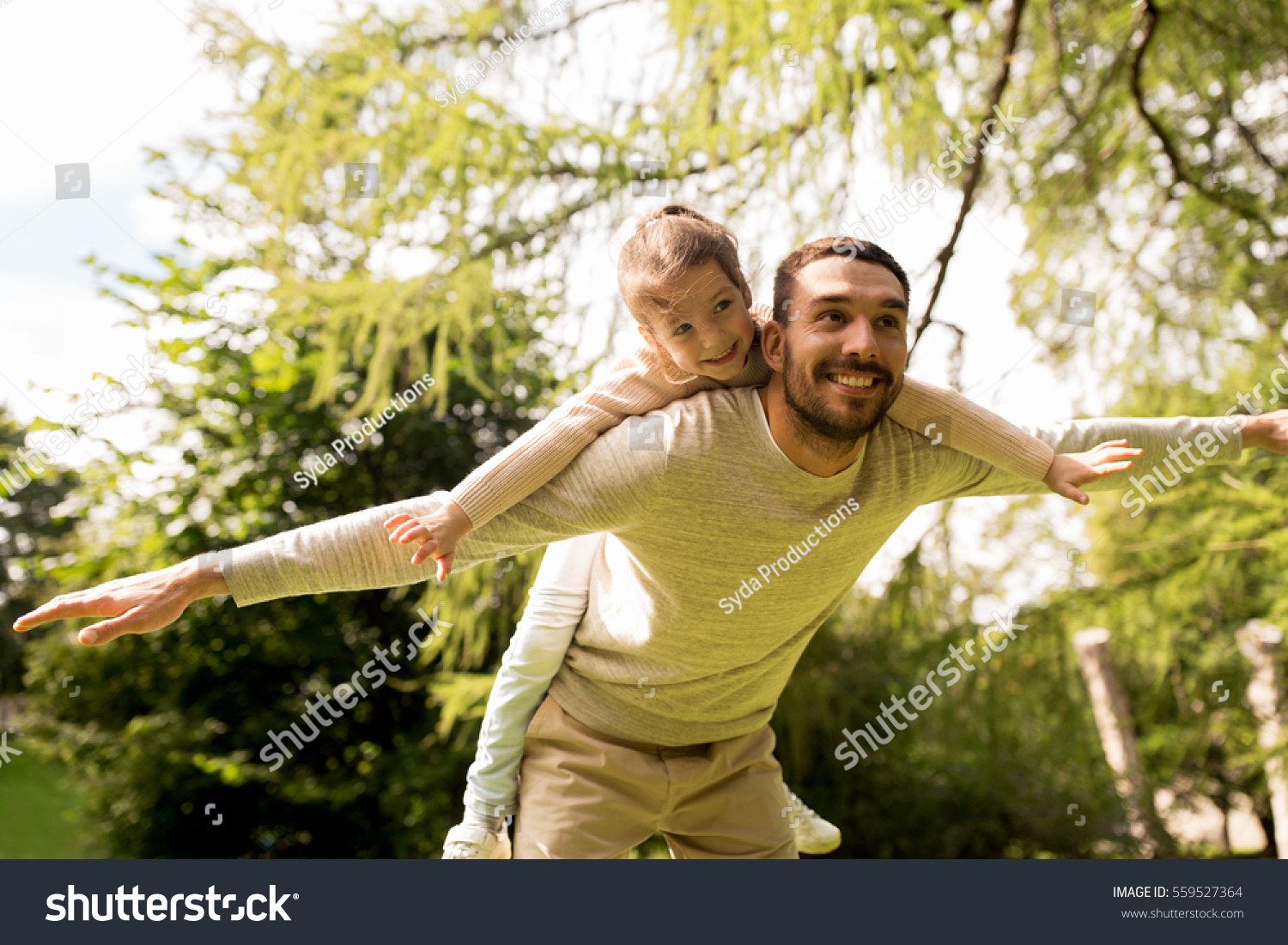 family, parenthood, fatherhood and people concept - happy man and little girl in having fun in summer park #559527364