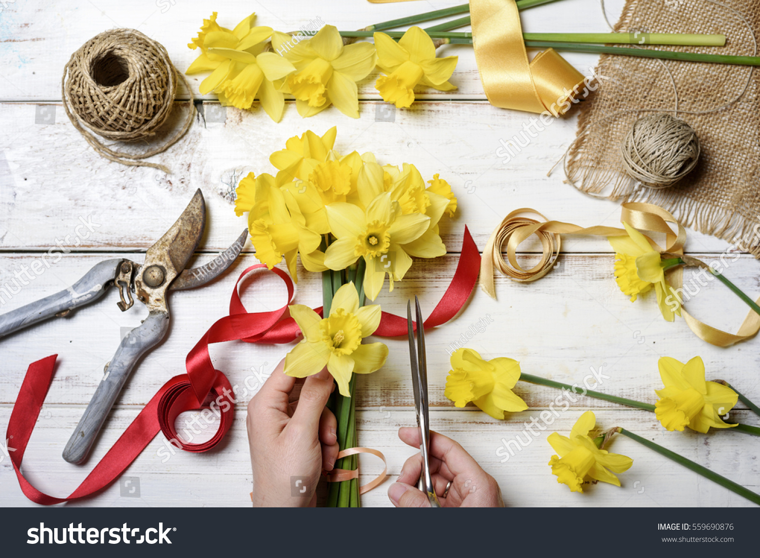 Top view florist hands making flower stock photo edit now top view of florist hands making flower bouquet with narcissus and decorative ribbon izmirmasajfo