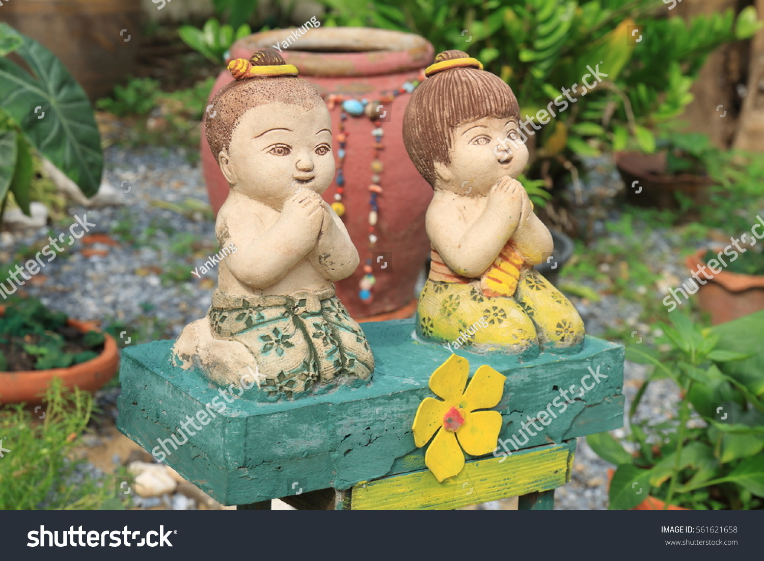 Porcelain thai doll on grass field stock photo 561621658 porcelain thai doll on grass field with hands pressed together in traditional thai greeting gesture kristyandbryce Images