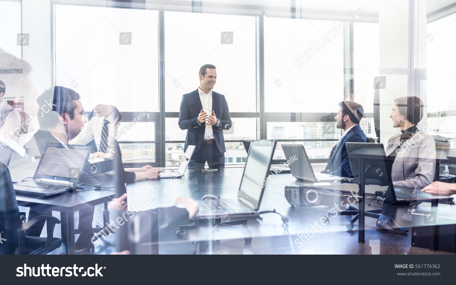 Successful team leader and business owner leading informal in-house business meeting. Businessman working on laptop in foreground. Business and entrepreneurship concept. #561776362
