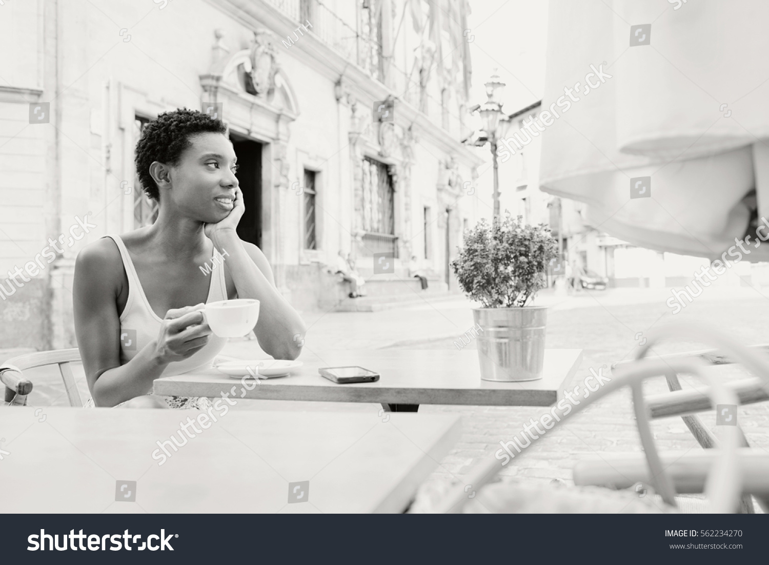 Black and white portrait of beautiful african american professional woman sitting in coffee shop terrace drinking