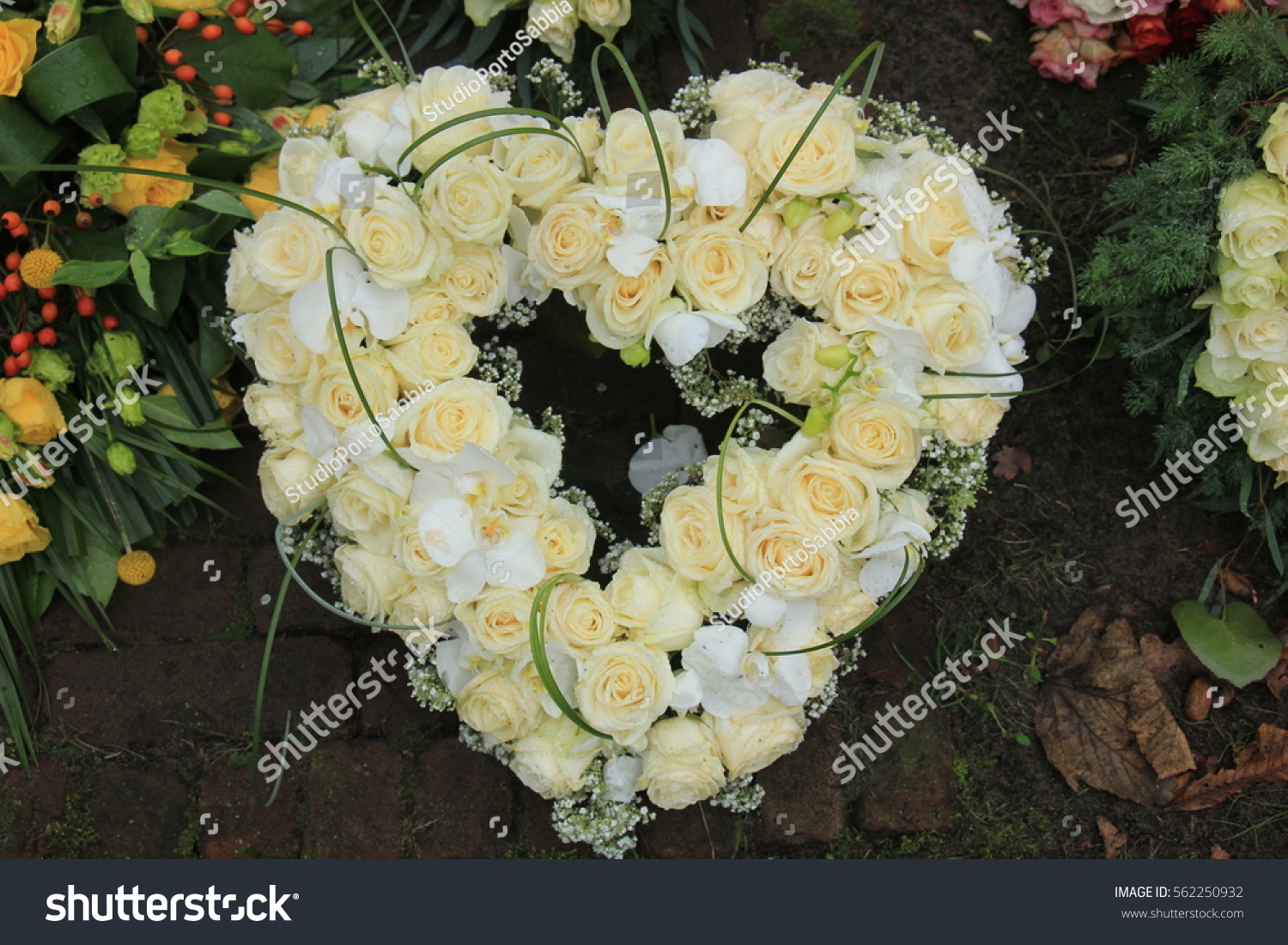 Heart shaped sympathy funeral flowers near stock photo 562250932 heart shaped sympathy or funeral flowers near a tree at a cemetery izmirmasajfo Gallery