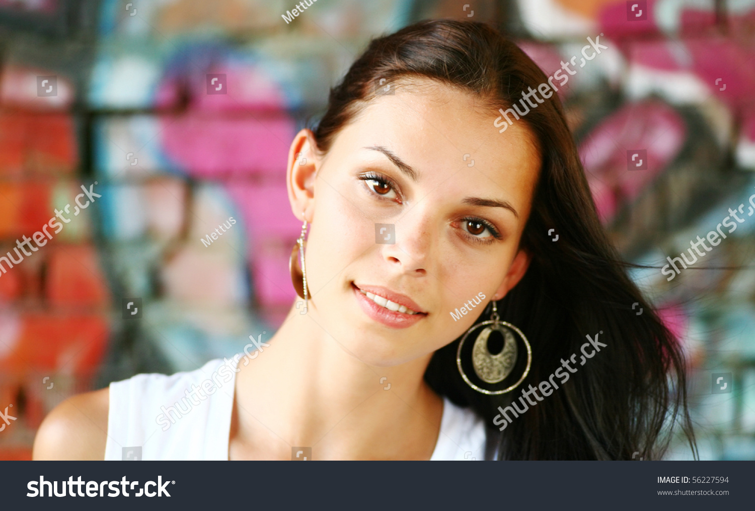 face of pretty brunette against colorful graffiti wall