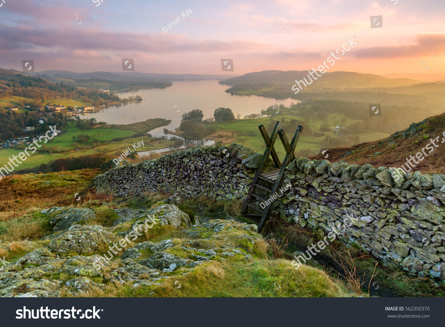 Beautiful sunset over Windermere in the Lake District with a stile and stone wall in the foreground. #562350370