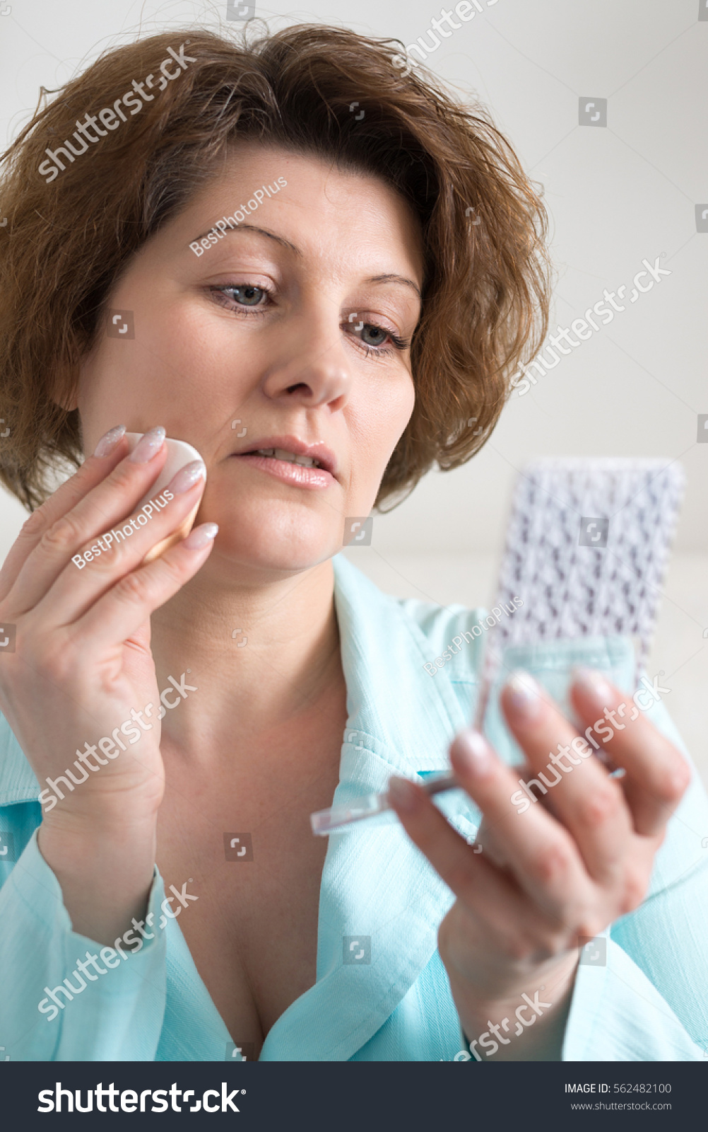 Woman puts makeup on face yourself stock photo edit now 562482100 woman puts makeup on the face of yourself solutioingenieria Image collections