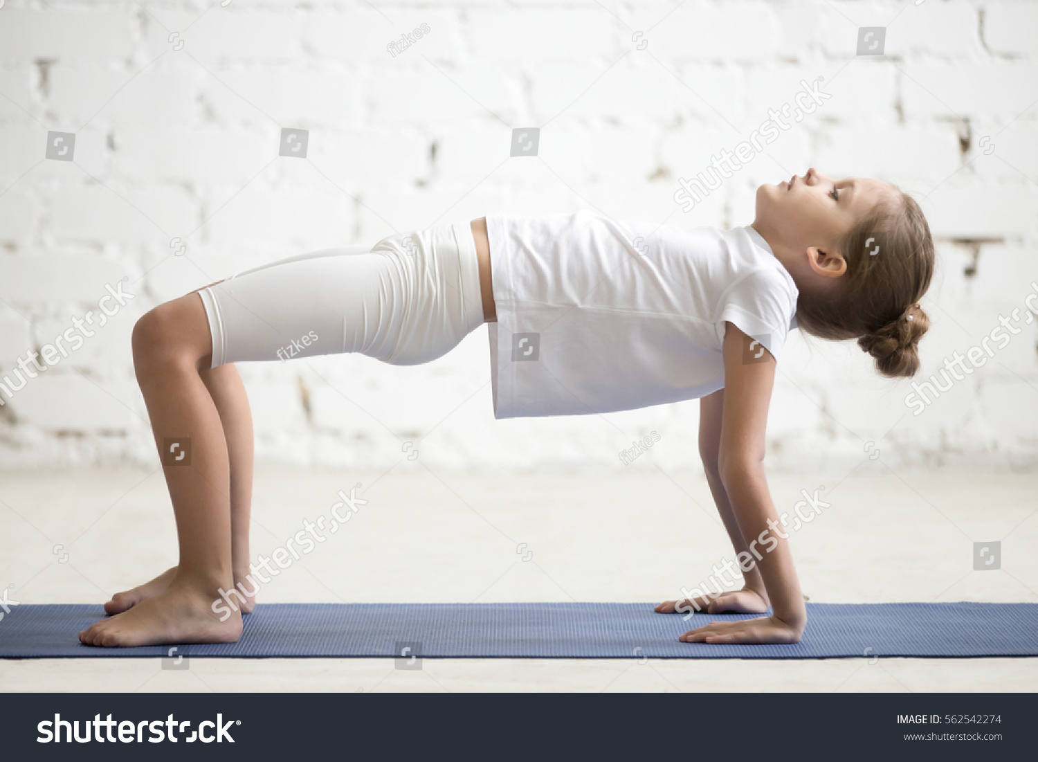 Serious girl child practicing yoga standing arkivbilde for Table yoga pose