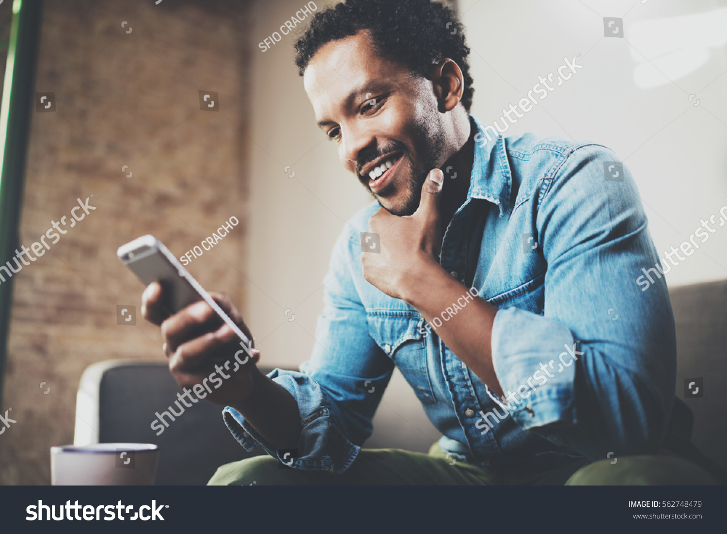 Happy bearded African businessman using phone while sitting on sofa at his modern home.Concept of young people working mobile devices.Blurred background #562748479