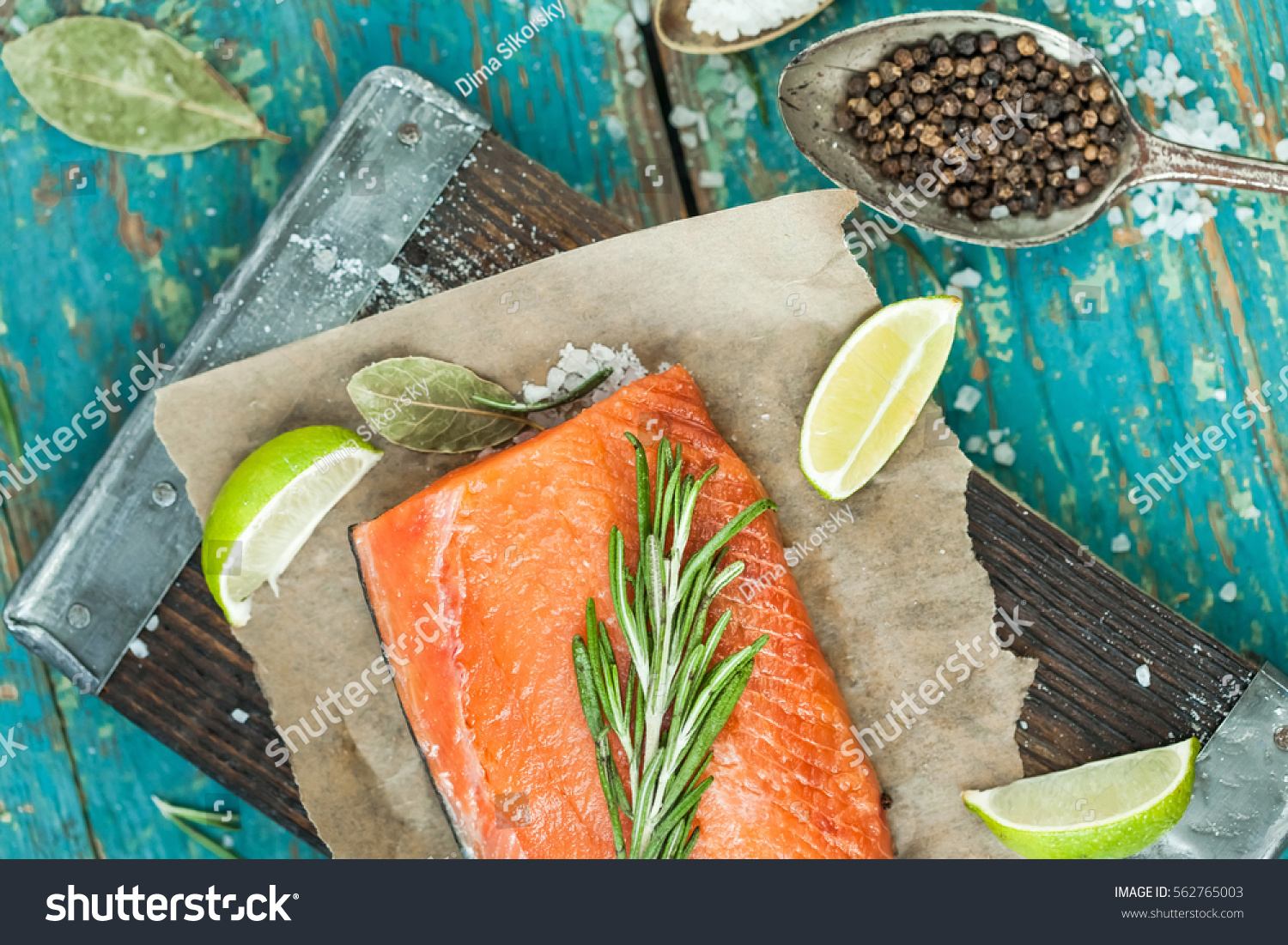 piece of raw salmon, spices, knife, board, spoon, olive oil, lemon ...
