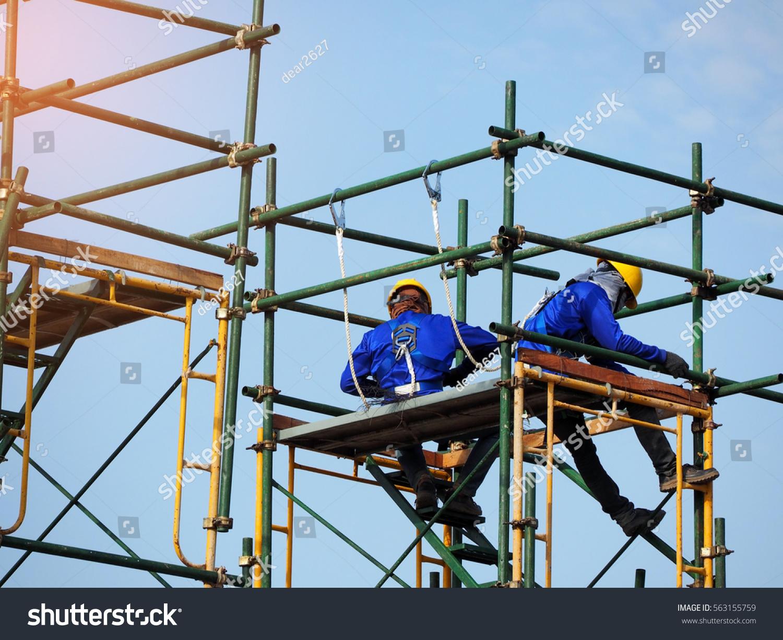 Working On Scaffolding : Construction workers working on scaffoldingman