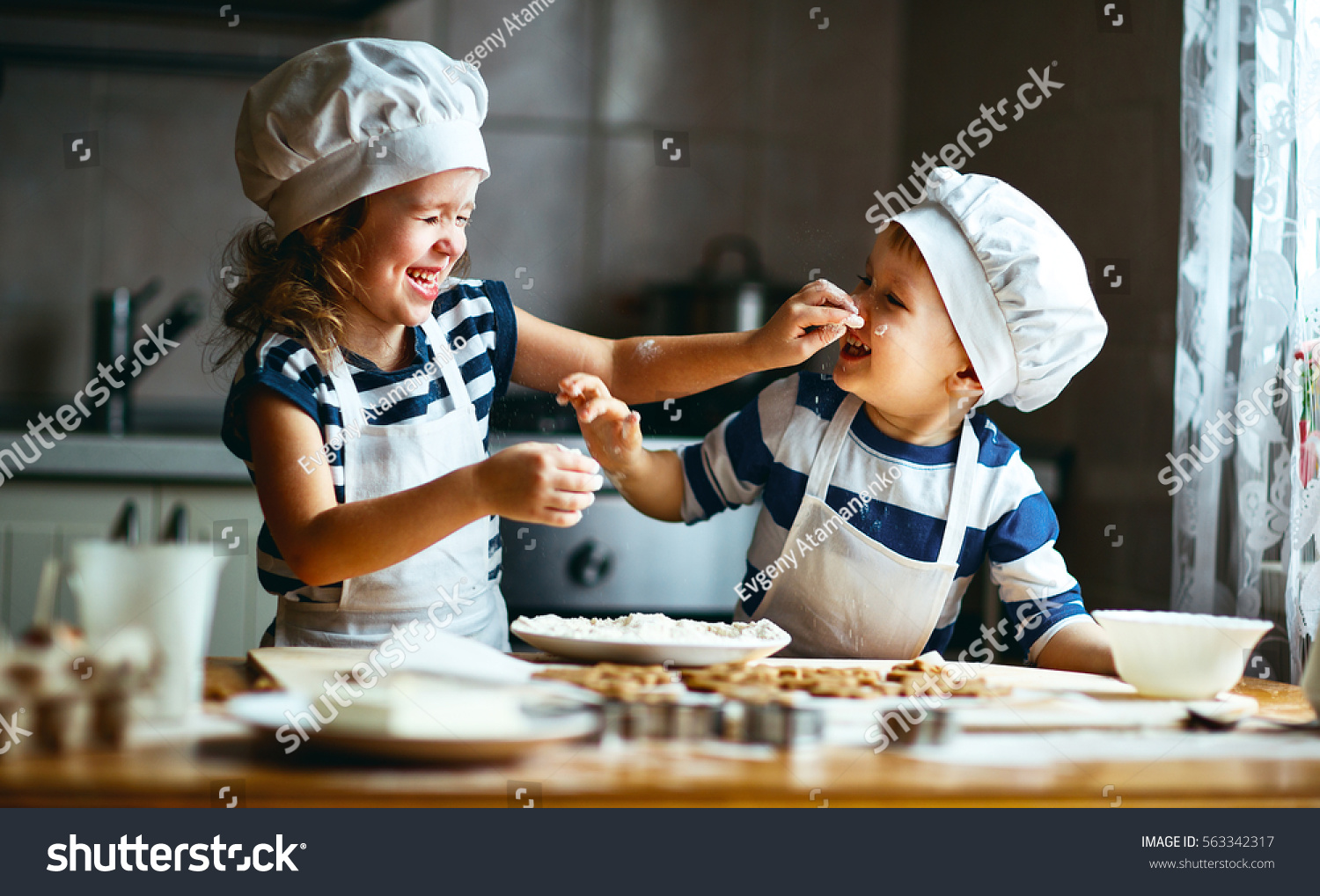happy family  funny kids are preparing the dough, bake cookies in the kitchen #563342317