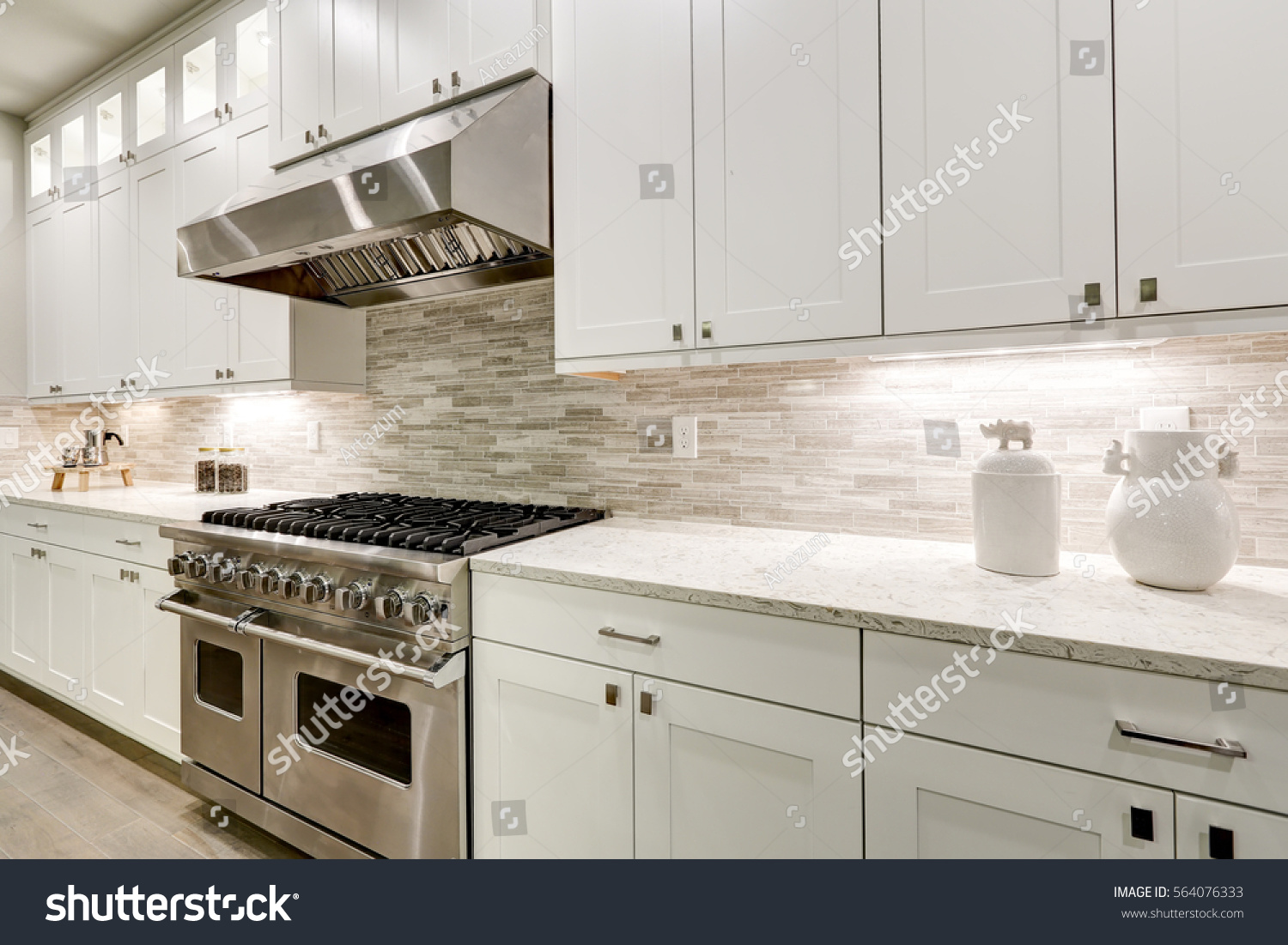 Gourmet Kitchen Features White Shaker Cabinets With Marble Countertops  Paired With Stone Subway Tile Backsplash And
