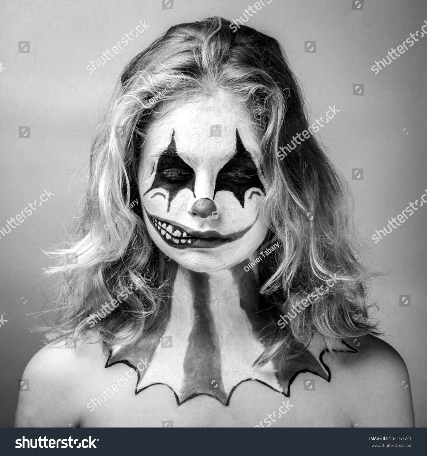 Portrait of a blond girl made up in joker with a fake smile on half of