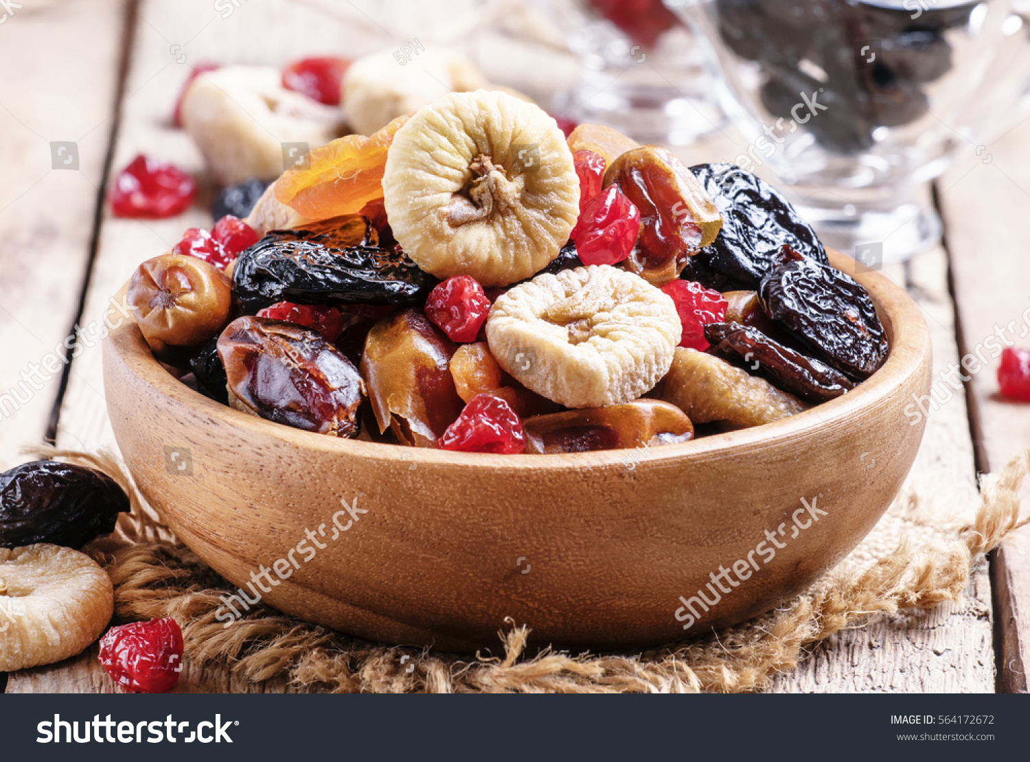 Healthy food: mix from dried fruits in bowl, old wooden background, selective focus