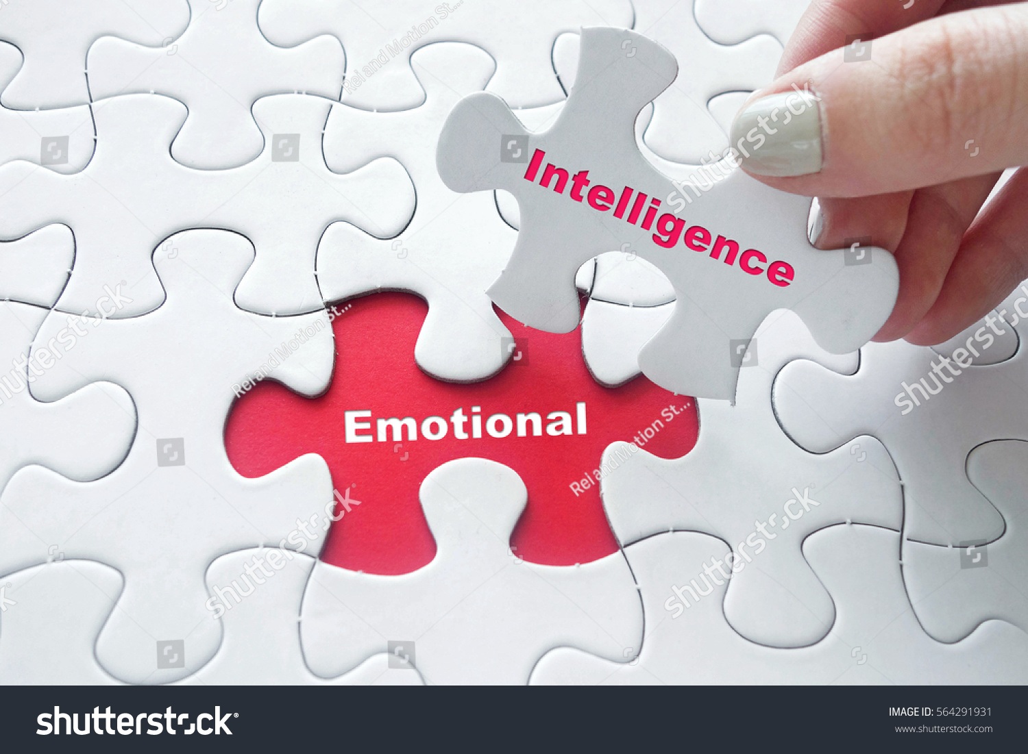 Close up of girl's hand placing the last jigsaw puzzle piece with word Emotional Intelligence #564291931