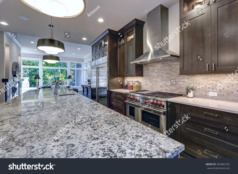 Modern Kitchen With Brown Kitchen Cabinets, Oversized Kitchen Island,  Granite Countertops, Stainless Steel