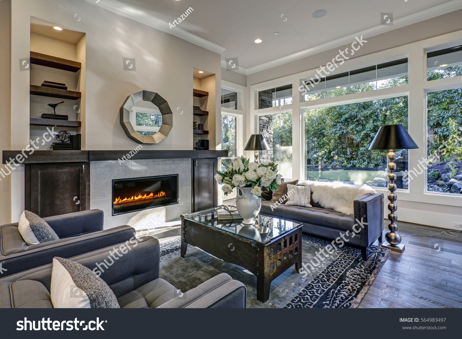 chic living room. chic living room filled with built-in cabinets flanking round mirror atop grey tile fireplace