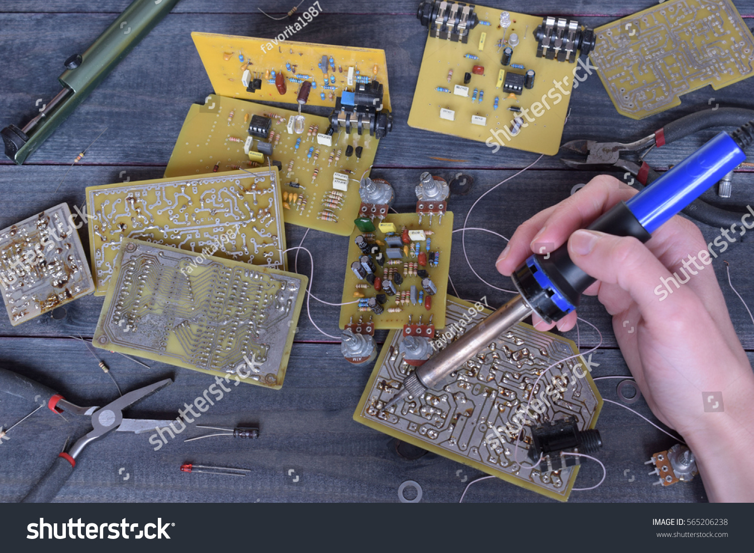 Soldering Tools Hand Holding Iron Stock Photo Edit Now Circuit Boards With Clock Hands Royalty Free Image A And Micro Circuits On The Wooden Background