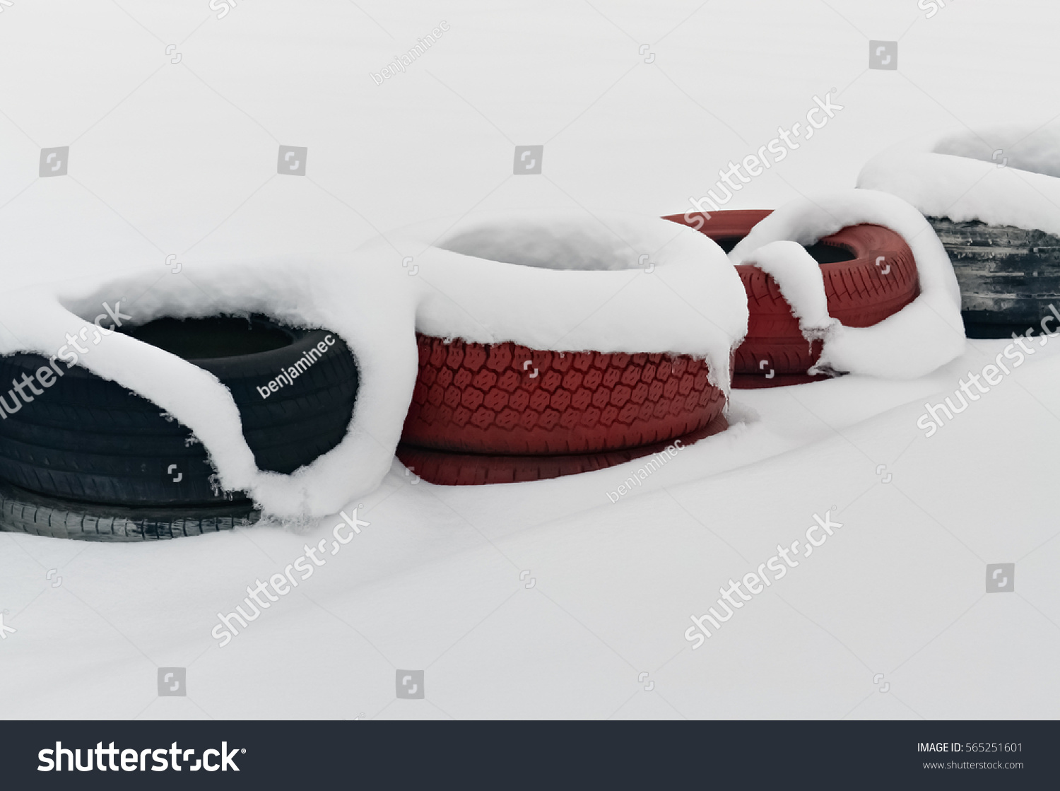 Several car tires under snow as a safeguard on the racetrack #565251601