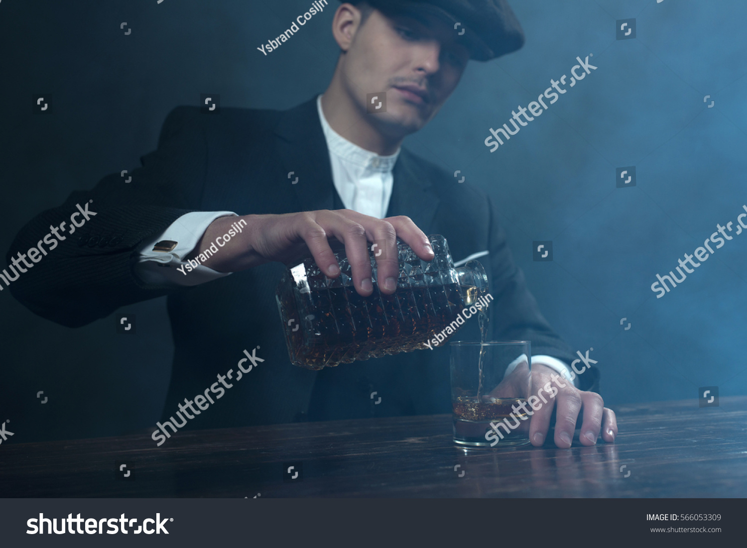 Retro 1920s english gangster with flat cap pouring whiskey. Peaky blinders  style. 10ed7cdd361