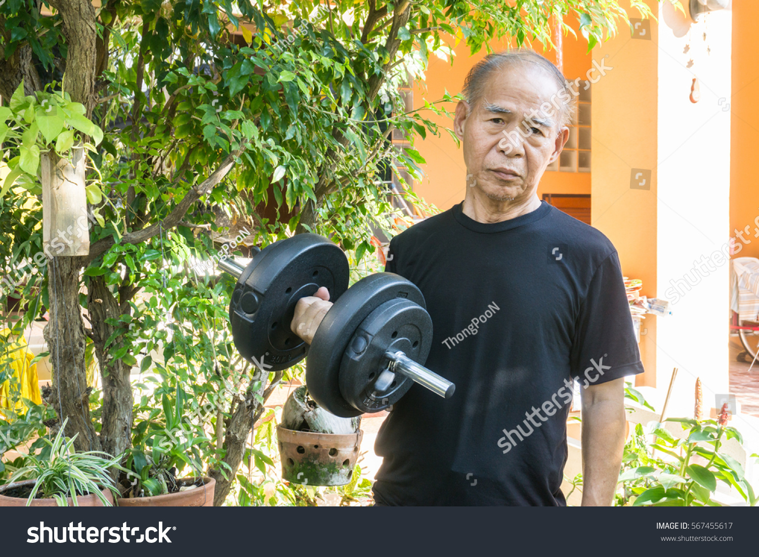 Old asia man with dumbbells. Person doing exercise outdoor. Strengthen the  muscles. Your