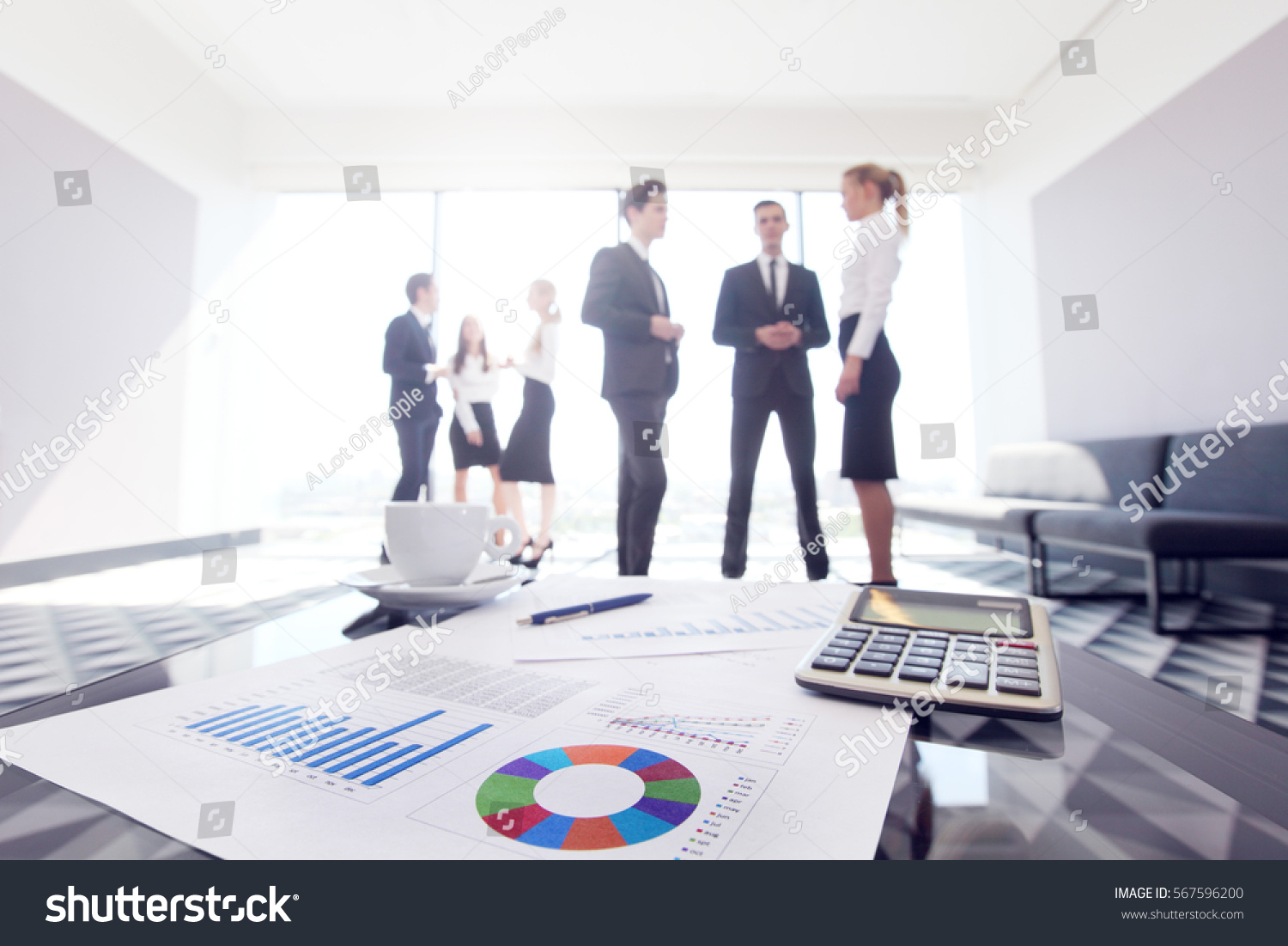 Business Documents On Office Table And Team Of People Background