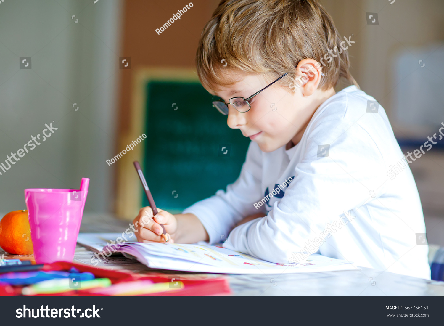 9024033b1a3 Portrait of cute happy school kid boy with glasses at home making homework. Little  child