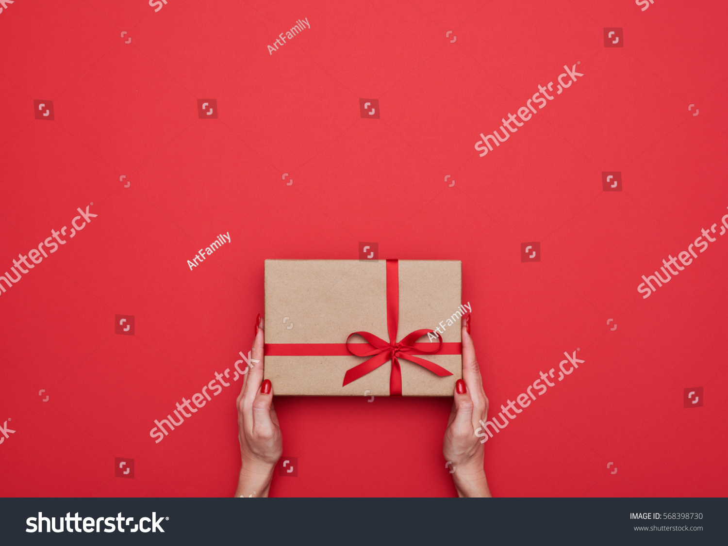 Top view of female hands holding present box package in the palms isolated over flat lay background  #568398730