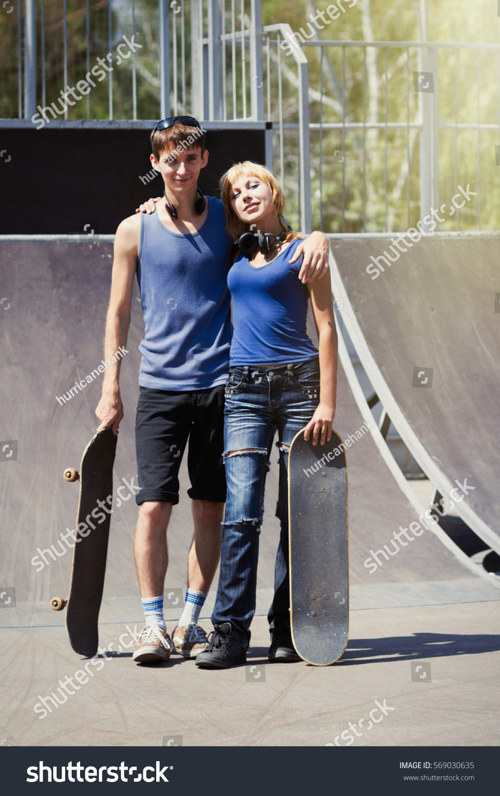 25a30e8b32 Young skater boy   girl embracing outdoor in bright sunny summer  day.Skaters with skate boards posing in park outdoor.Active youth.