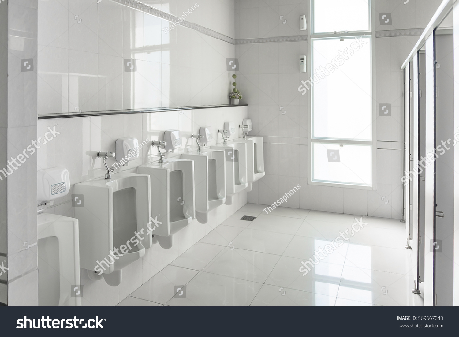 White Urinals In Clean Men Public Toilet Room Empty With Big Window And Light From Outside