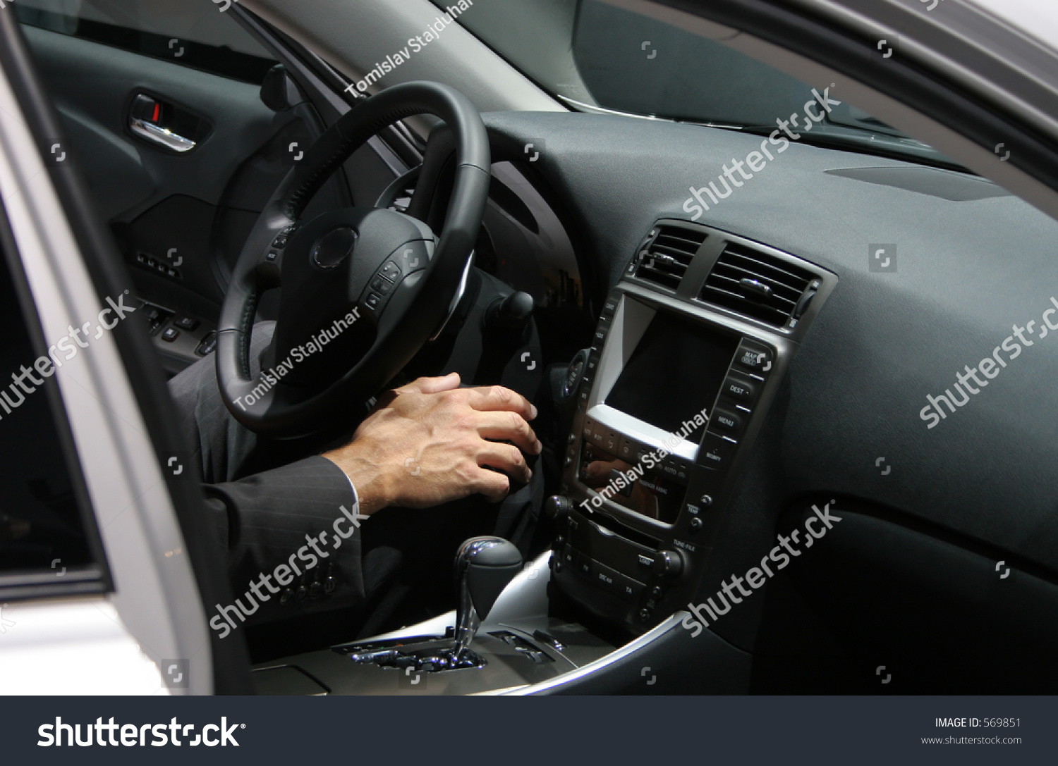 man 39 s hand in new car interior man wearing a business suit stock photo 569851 shutterstock. Black Bedroom Furniture Sets. Home Design Ideas